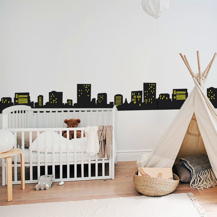 Sticker urbain immeuble au-dessus d'un lit bébé blanc et tente