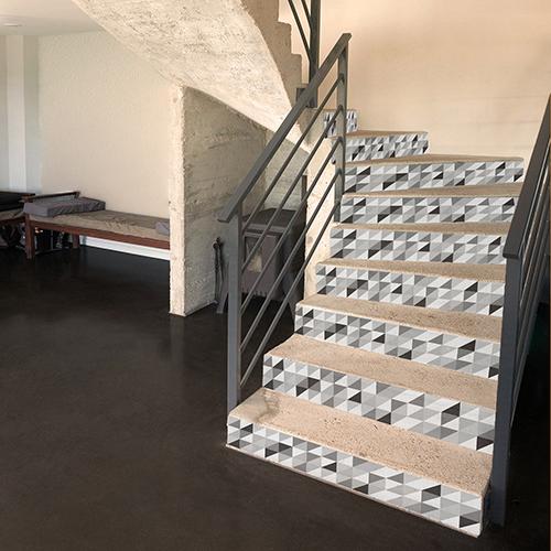 Stickers escaliers avec pour motif triangles emboités noir gris et blanc sur marches en pierre