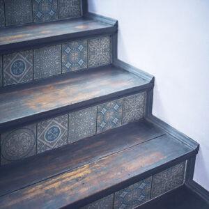 Egayez un esclaier en bois avec des contremarches adhésives pour escalier carreaux de ciment bleu et gris.