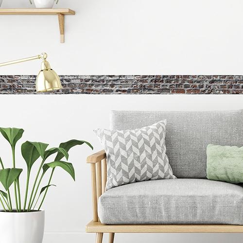 Sticker autocollant frise droite briques derrière un canapé
