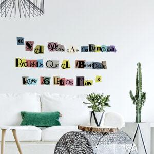 Citation murale multicolore SI EL PLAN collé au mur d'un salon avec des plantes