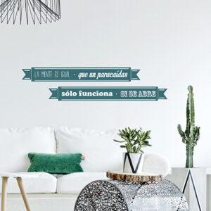sticker mural coloré citation en espagnol collé au mur d'un salon moderne avec des plantes