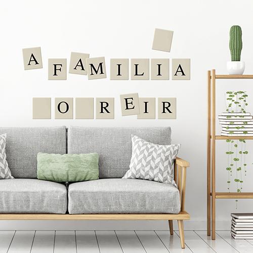 Citation sur la famille avec des lettres de scrabble stickée au mur d'une pièce à vivre blanche