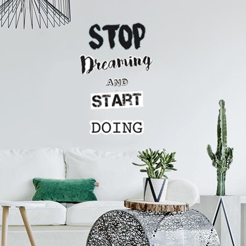 Sticker citation Stop dreaming motivante collé au mur d'une pièce à vivre moderne