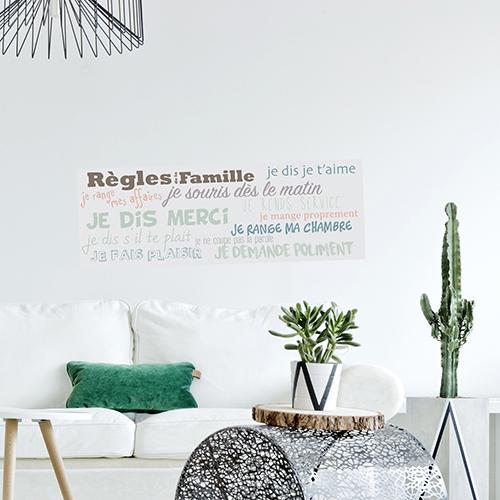 Sticker mural règles de la famille collé au mur d'un salon morderne avec des plantes exotiques