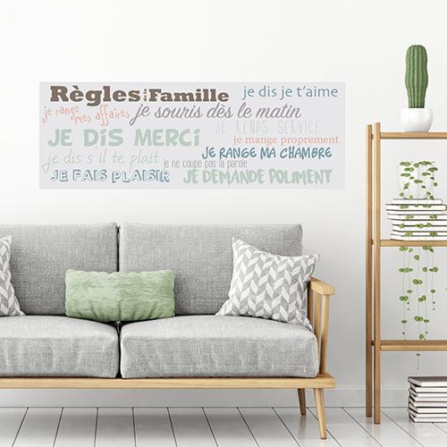 Mur d'un sallon orné d'un sticker adhésif mural donnant les règles de la famille.