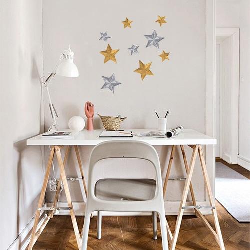Sticker étoiles or et argent collé au mur d'un petit bureau