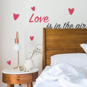 Sticker Love is in the Air collé au mur d'une chambre d'adultes