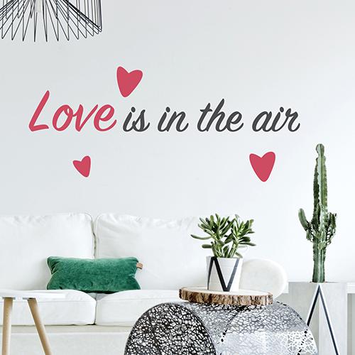 Citation d'amour Love is in the Air collé sur le mur d'une pièce à vivre