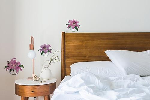 Sticker autocollant fleur de lys rose au dessus d'un lit