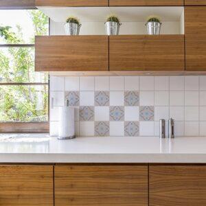 Autocollant ciment fleur bleu, orange et marron pour déco carrelage blanc dans une cuisine