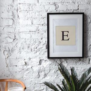 """Adhésif lettre """"E"""" beige et noir alphabet pour déco de cadre sur un mur blanc"""