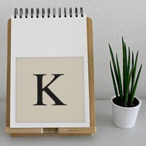 """Autocollant décoration lettre """"K"""" alphabet beige et noir pour agenda sur un meuble"""