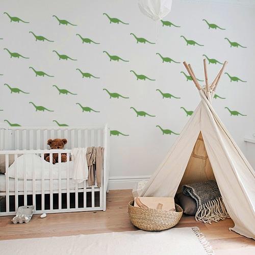 Multitude de petits dino verts foncés collés au mur d'une salle de jeux pour enfants
