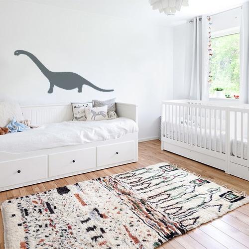 Chambre d'enfant avec un mur orné d'un sticker dino gris géant