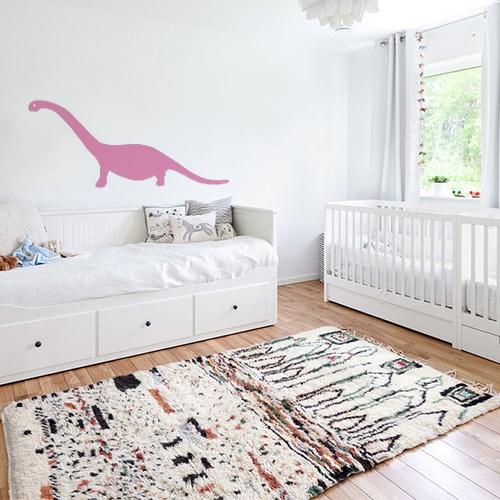 sticker géant dino rose collé au mur d'une chambre pour décorer