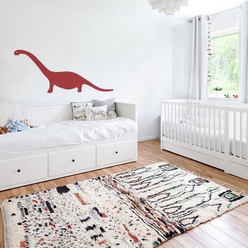 Dinosaure géant rouge stické au mur d'une chambre