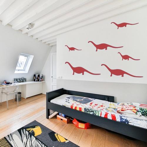 5 stickers dino rouges posés au mur d'une chambre pour enfants