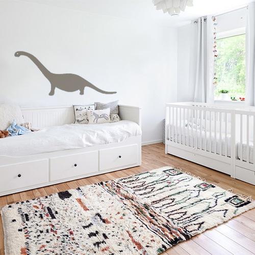 Dino géant couleur taupe collé sur un mur blanc pour décorer