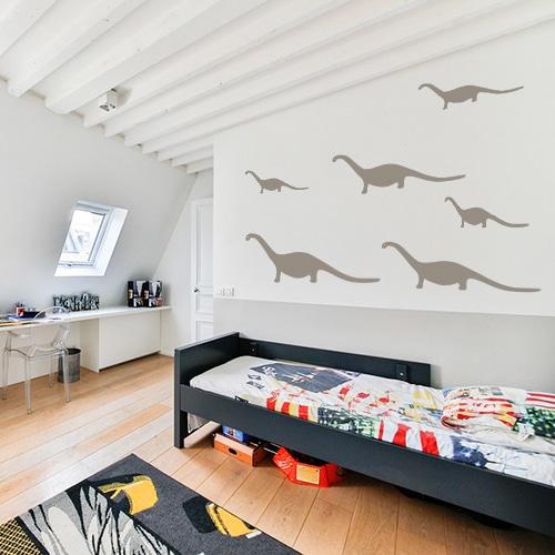 Famille de dino couleur taupe stickée sur le mur d'une chambre d'enfant