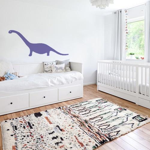 sticker dino violet géant collé au mur d'une chambre d'enfant