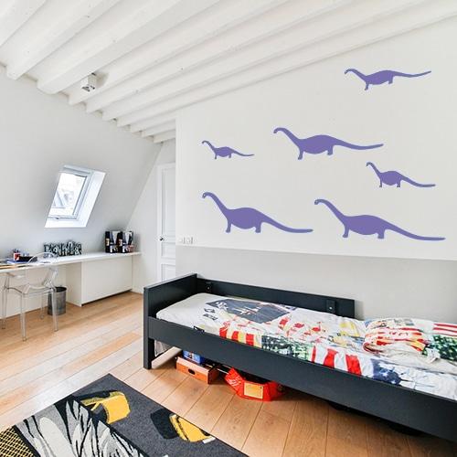 5 stickers dino violets de tailles variée collés au mur d'une chambre d'enfant