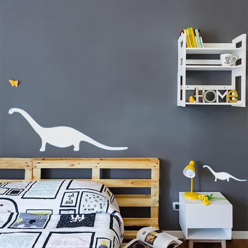 Sticker dinosaure gris clair collé sur le mur gris foncé d'une chambre à coucher
