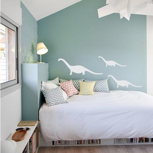 Ensemble de trois stickers dino gris clair collés au mur d'une chambre