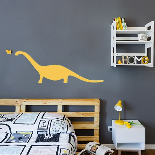 Sticker autocollant dinosaure jaune collé au mur gris foncé d'une chambre