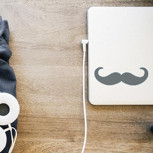 sticker décoratif moustache grise foncée en croc posée sur un pc portable