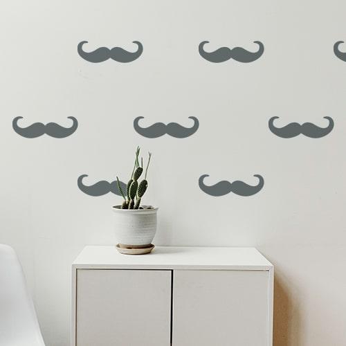 Ensemble de petites moustaches en croc couleur grise foncée stické sur un mur blanc
