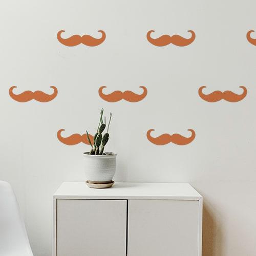 Frise de stickers moustaches en croc orange collée au mur d'une pièce à vivre