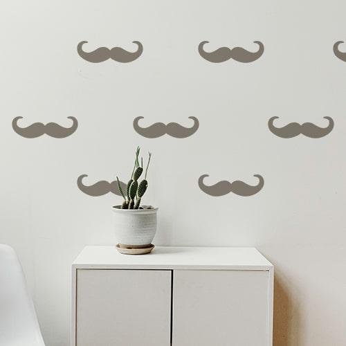 Frise de stickers adhésifs moustache en croc couleur taupe sur un mur blanc d'une pièce à vivre