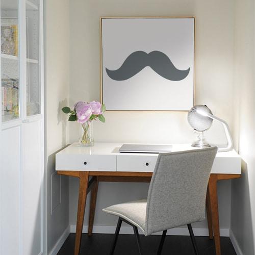 sticker moustache grise foncée collée sur un tableau mural