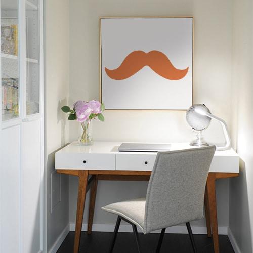 sticker moustache épaisse orange collé sur un tableau mural