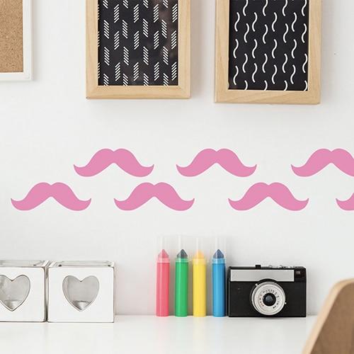 Frise de stickers moustache rose collés au mur d'une pièce