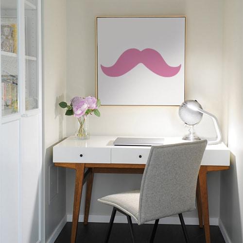 sticker moustache épaisse rose sur un tableau au mur