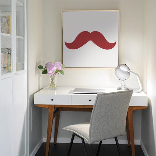 sticker mural moustache rouge sur un tableau au mur