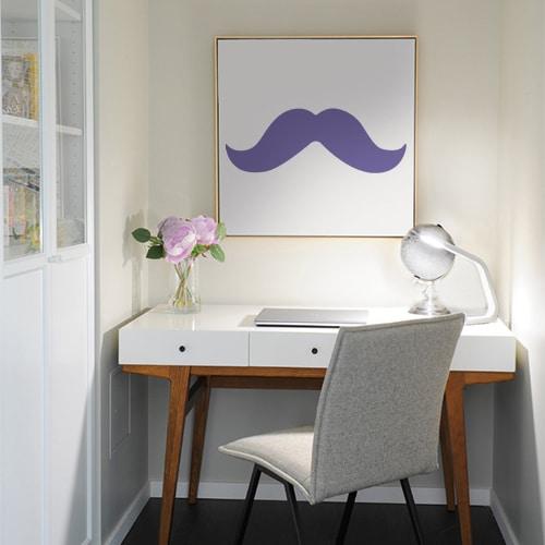 sticker décoratif moustache violette sur un tableau au dessus d'un bureau