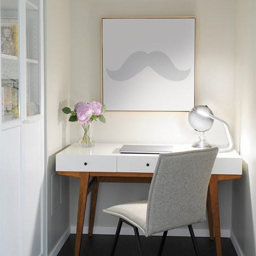 Sticker Moustache grise collé sur un tableau au dessus d'un bureau