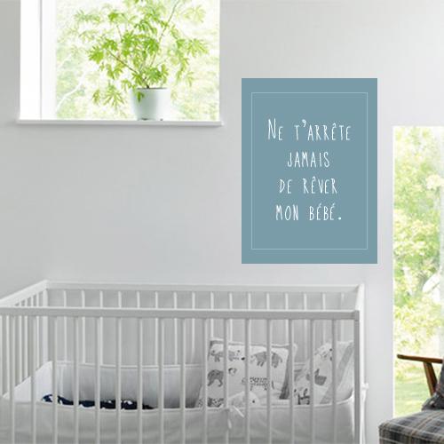 Sticker N'arrête jamais de rêver citation au dessus d'un lit de bébé