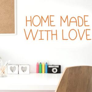"""Sticker adhésif citation orange pour décoration murale """"home made with love"""" au dessus d'un bureau blanc"""