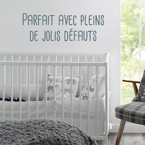 Sticker adhésif citation Parfait avec pleins de défauts au dessus d'un lit de bébé