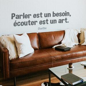 Sticker Parler est un besoin citation au dessus d'un canapé en cuir dans un salon