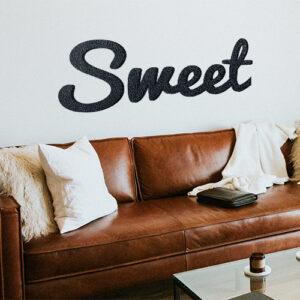 Sticker adhésif citation Sweet au dessus d'un canapé en cuir marron