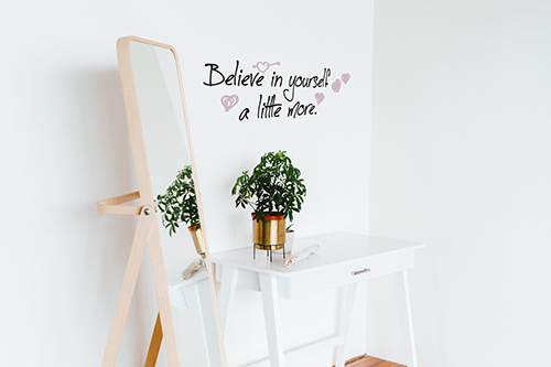 Sticker citation manuscrite Believe in yourself colorée collé au mur blanc d'un dressing