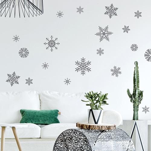 Sticker mural adhésif ensemble de flocons de neiges argentés collé sur le mur d'un salon