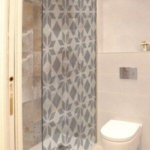 Sticker style moderne posée sur la vitre du douche dans une salle de bain avec WC