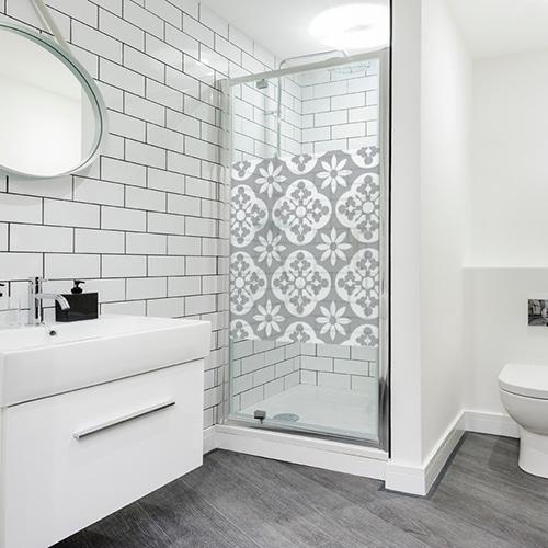Sticker carré style fleuri collé dans une grande salle de bain moderne et éclairée avec toilettes