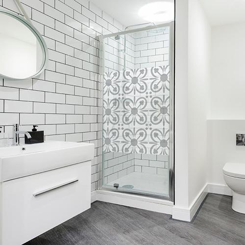sticker carré pétale de fleur collé sur une porte de douche dans une grande salle de bain moderne.